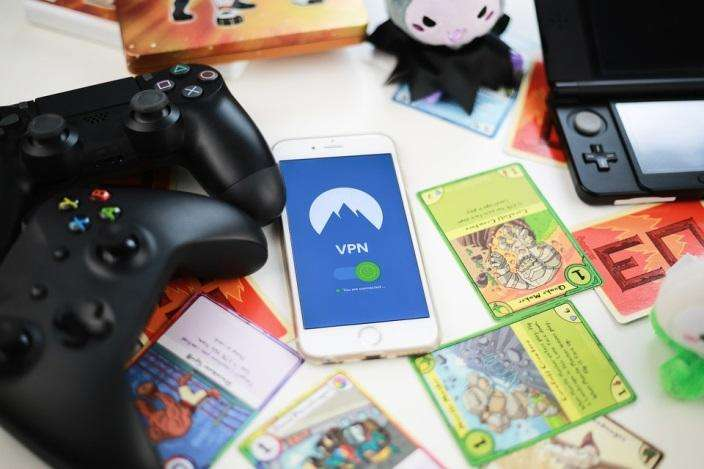 How WordPress Users Benefit From VPN: A smartphone showing a VPN, around trading cards, console controllers, and a handheld console.